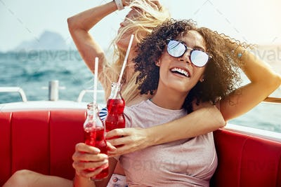 Laughing girlfriends having drinks on a boat during summer vacation