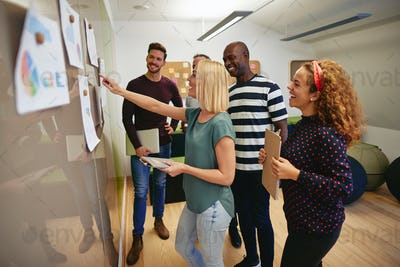 Smiling work colleagues reading paperwork together on an office wall