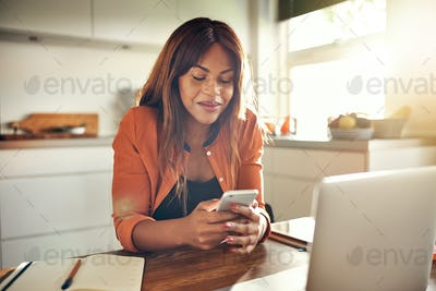Young entrepreneur sending text messages while working in her kitchen