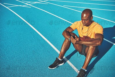 Runner sitting alone on an outdoor track listening to music