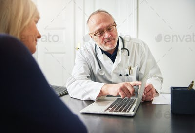 Woman listening to adult doctor explaining diagnosis with laptop