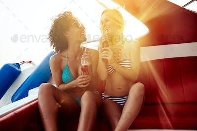 Smiling friends in bikinis sitting on a boat enjoying drinks