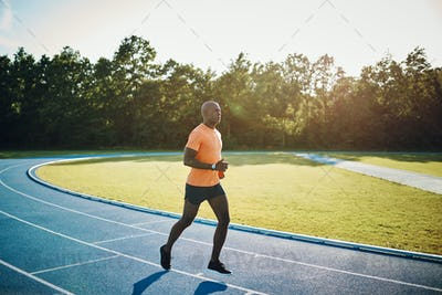 Young athlete running alone on a race track