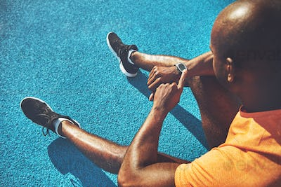 Young runner sitting on a track checking his fitness watch