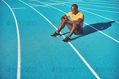 Young African athlete listening to music before a run