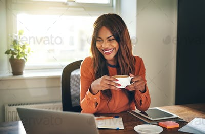 Laughing young woman drinking coffee while working from home