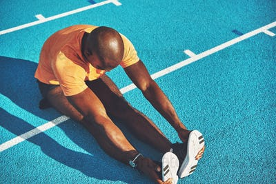 Young athlete warming up on a running track before training