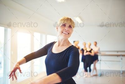 Smiling mature woman practicing ballet in a dance studio