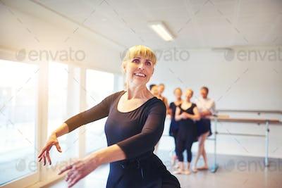 Smiling mature woman ballet dancing in a studio