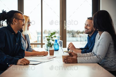 Smiling business colleagues meeting around a table in an office