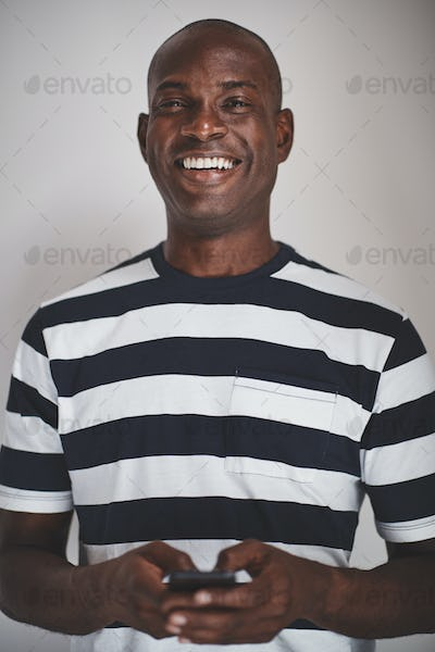 Laughing African entrepreneur using his cellphone against a gray background