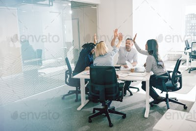 Smiling coworkers sitting around an office table high fiving together