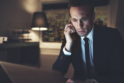 Intelligent businessman talking smartphone and surfing laptop