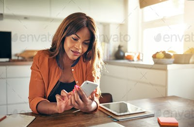 Young entrepreneur reading texts while working at her kitchen table