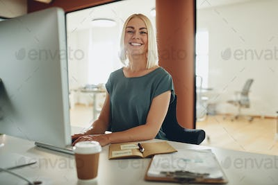 Young businesswoman smiling while working at her office desk