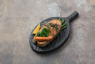 Fried salmon steak with vegetables on wooden board, copy space