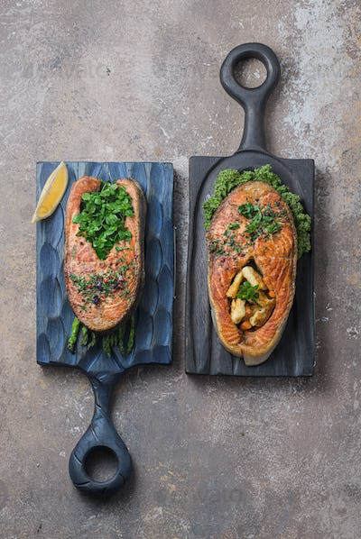 Two salmon steaks with vegetables on wooden boards, top view copy space