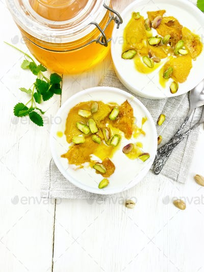 Dessert of yogurt and persimmon two bowls on light board top
