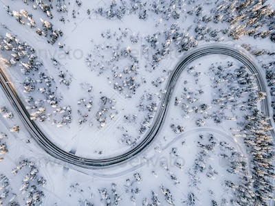 Aerial view of Curvy Windy Road in snow covered forest in Winter Finland