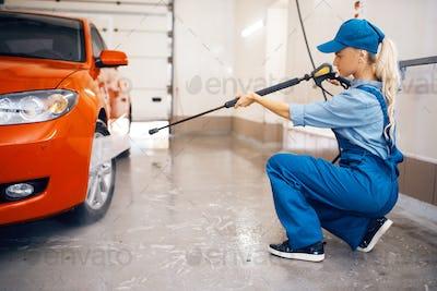 Female washer cleans wheel with high pressure gun