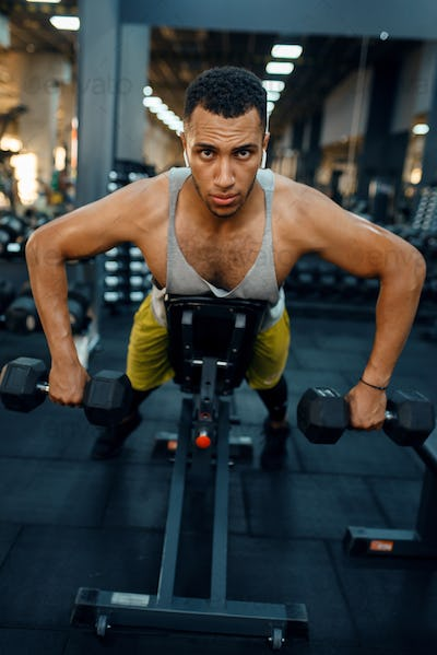 Man doing exercise with dumbbells on the bench