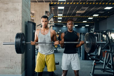 Two muscular men poses with heavy barbell in gym