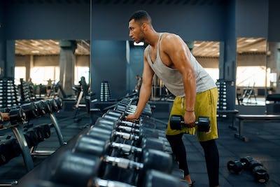 Muscular man choosing heavy dumbbells in gym