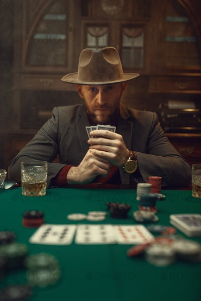 Poker player in suit and hat plays in casino