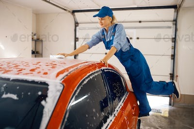 Female washer wipes the automobile windshield