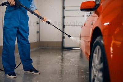 Female washer with high pressure gun, car wash