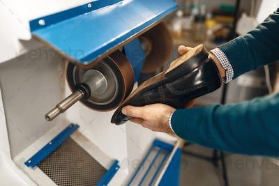 Shoemaker processes women's shoes on emery machine