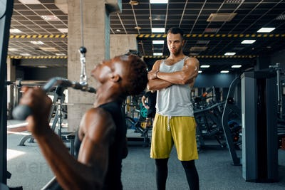 Muscular man and his instructor, training in gym
