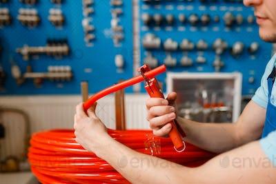 Plumber cuts plastic pipe, plumbering store
