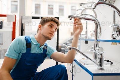 Plumber in uniform at showcase in plumbering store