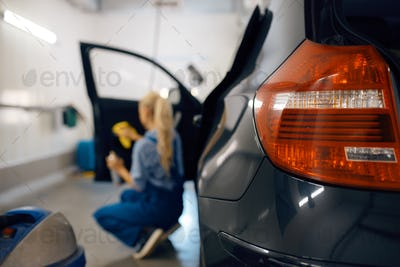 Female washer cleans automobile door trim