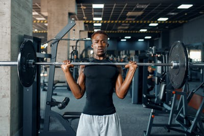 Athlete doing exercise with barbell in gym