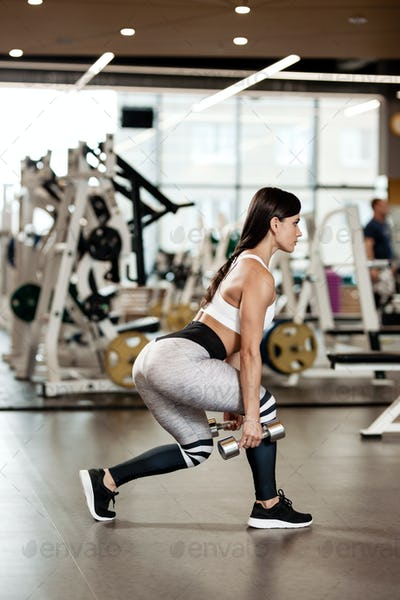 Slim brunette girl dressed in a sportswear is doing squats with dumbbells in the modern gym