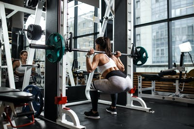 Young athletic girl dressed in sportswear squats with a barbell in the modern gym