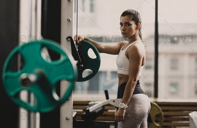 Athletic girl dressed in sportswear prepares the barbell to lift weight in the modern gym