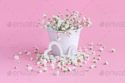 Small white flowers and hearts on a pink background