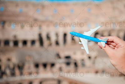 Closeup toy airplane on Colosseum background. Italian european vacation in Rome. Concept of