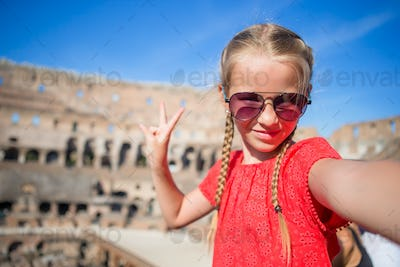 Little girl making selfie in Coliseum, Rome, Italy. Kid portrait at famous places in Europe