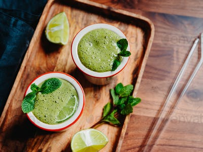 Two portions of green spinach smoothie with banana, lime and oat mil