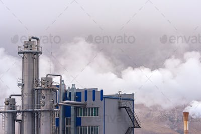Air pollution by factory smoke. Grey factory against cloudy sky