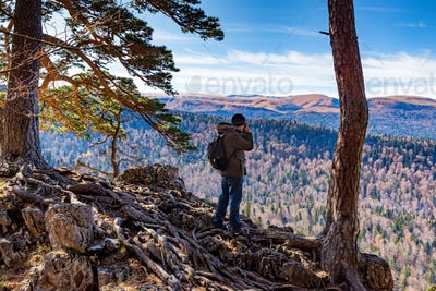 Male hiker takes photo of beautiful mountains in autumn. North Caucasus