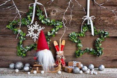 Christmas composition with a gnome on sleigh and festive decorations