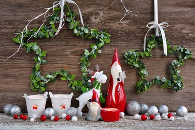Christmas composition with gnomes, elk figurine and festive decorations on wooden background
