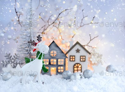 Christmas composition with decorative elk, huts and festive decorations on the snow