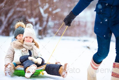 Little girls enjoying sledding. Father sledding his little adorable daughters. Family vacation on
