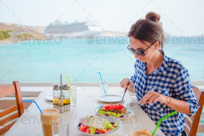 Young woman having lunch with delicious fresh greek salad, frappe and brusketa served for lunch at